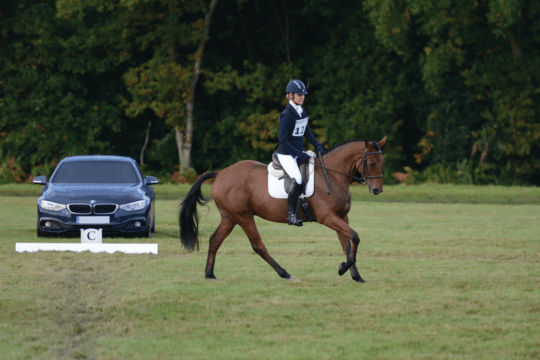 riding a dressage test in front of a judge