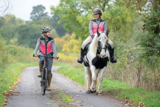Horse rider and cyclist densensitising horse to the bike