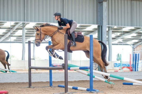 Emily King jumping an Oxer as part of a grid