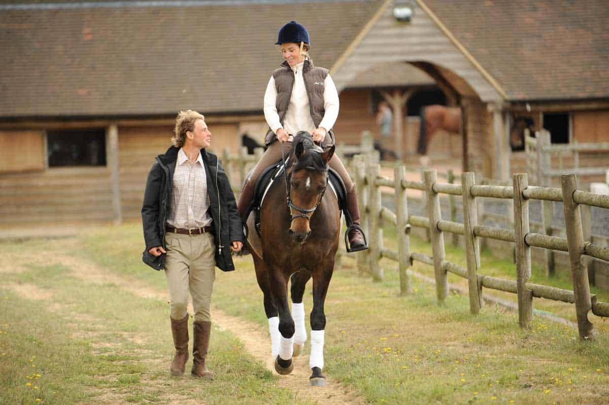 Woman riding horse and man  walking alongside