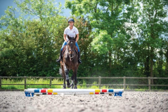 Showjumper Anna Power riding a raised pole exercise