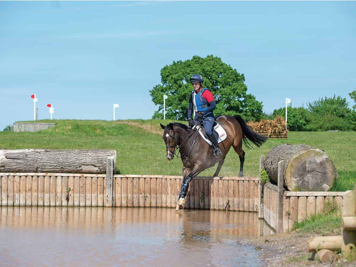 Tina Cook jumping into a cross-country water jump