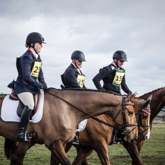 Eventing, three riders at an event walking together to a warm up