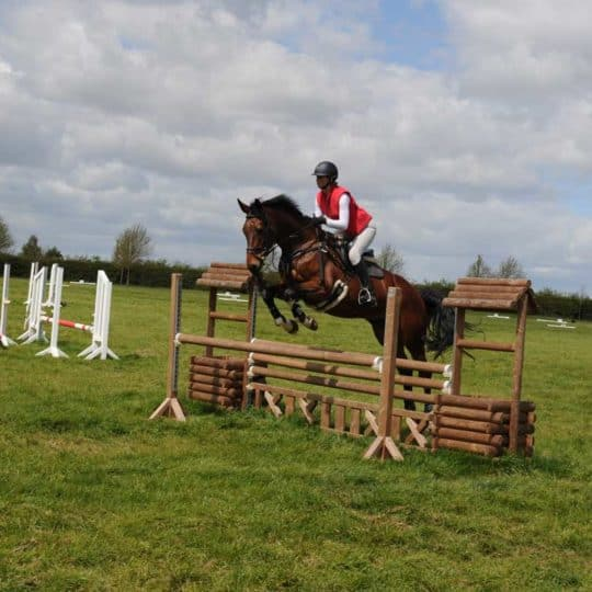 Horse and rider jumping rustic fence